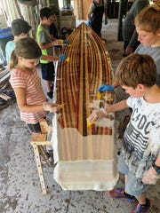 Campers add a fiberglass coating to the bottom of the paddle board.