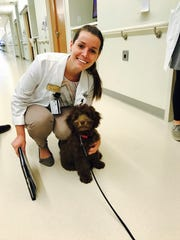 Sarah Cummins takes a break with a therapy dog during one of her pharmacy school rotations.