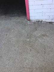 A photograph sent by Tom Kraft's attorney allegedly showing a bullet mark on the ground outside of Kraft 5 Star Muffler.