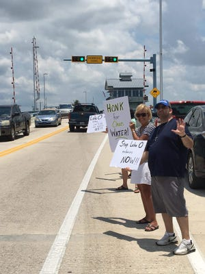 A handful of Pine Island residents took to the Matlacha Bridge on Sunday to protest the release of water from Lake Okeechobee and a bloom of blue-green algae in area waterways linked to that release.