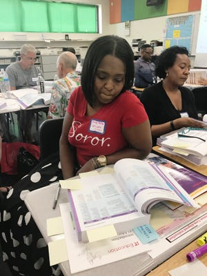 Detroit Public Schools Community District teacher Brandy Walker follows along in a text book during  training on the district's new curriculum at Martin Luther King Jr. High School in Detroit on July 17, 2018. Walker, a 5th grade reading teacher at the Foreign Language Immersion Cultural Studies school, became a Master Teacher at DPSCD this year. She plans to teach her regular class a half day this school year and use the other half as a master teacher to support the other teachers.