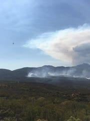 An airplane drops retardant on the Ribbon Fire burning