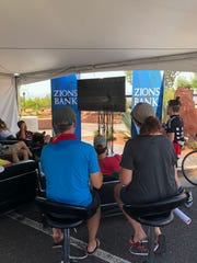 Patrons cool down under a tent to watch the Tour of Utah prologue at the KUTV 2 Healthy Living Expo in St. George on Aug. 6, 2018.