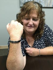 In this Monday, April, 15, 2019 photo, Jackie Fakler, co-owner of RJR Maintenance and Management in Mandan, North Dakota, displays a wrist band someone sent her anonymously to show support after the slayings of four people at RJR on April 1, 2019. The dead included Fakler's husband, Robert. The wrist band is ornamented with the first initials of the four victims, along with charms associated with each.