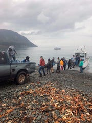 Residents of Nanwalek, Alaska, unload 65-gallon water jugs delivered to the Kenai Peninsula community by water taxi.