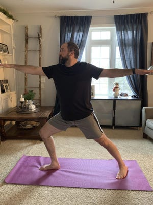 Steve Latart does yoga exercises last week at his home in Rogers, Minnesota. LaTart's yoga and warrior sculpting instructors at Life Time Fitness in Minneapolis are still teaching classes. They've just moved them from the gym to cyberspace, where they are livestreaming instructions from their website. LaTart says knowing he can still participate in the classes is keeping him sane.