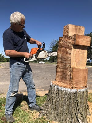 TMP-Marian maintenance worker Steve Werth began carving Saturday on a cedar tree stump on the campus to create the Catholic school's logo.