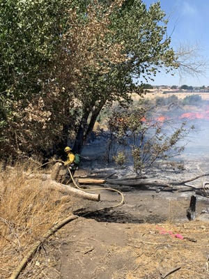 A firefighter on Monday works to contain a vegetation fire in the Mojave River bottom near Sitting Bull Road in Apple Valley.