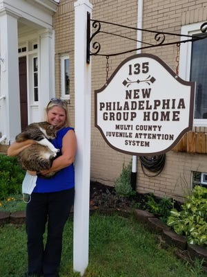 New Philadelphia Girls Group Home Administrator Lisa Green holds Moe, a former stray said to know when residents need comfort.
