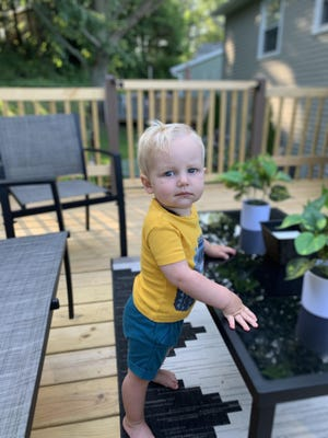 Benjamin LaFuria hangs out at the new outdoor seating area and deck that his dad, Christopher LaFuria, built.