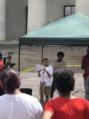 Matthew Williams, 13, speaks at a Youth on Fire rally outside the Statehouse on Friday.