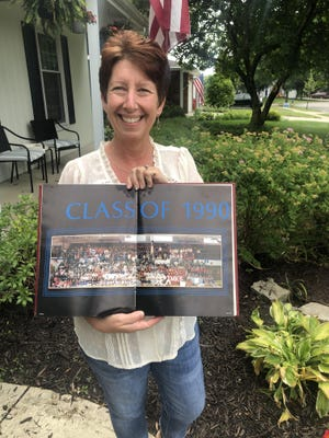 Christy DeWees poses at her Worthington home with a yearbook photo of her 1990 graduation class from Worthington High School. Her 30th reunion was canceled due to COVID-19.