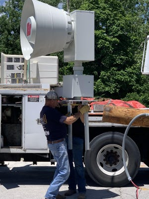 Workers take measurements on the city's new emergency siren, which was installed near the Moberly Area Community College on Wednesday afternoon.