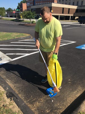 Gregory Page sweeps up cigarette butts from the parking lot of the Howard T. Brown Memorial Park on Saturday.
