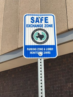 Signage for the new Safe Exchange Zones parking spaces near the Lubbock police department at 10th Street and Texas Avenue.