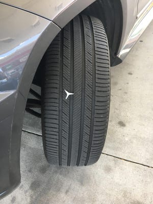 A spike rests in the tire of a car belonging to Providence Councilman John Igliozzi, whose home and car and son's car were vandalized over the weekend.