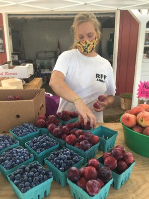 Anna Riegel packs fruit at the Riegel Farm and Forge farm stand on Wednesday. She started the stand with her husband, Mike Riegel, this year, taking over the location of the Parkhurst Farm Stand.