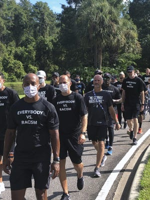 NBA referees march Thursday in support of players seeking an end to racial injustice in Lake Buena Vista, Fla., Their march occurred shortly before players met to decide their next steps before considering whether to restart the season after games were postponed Wednesday and Thursday.