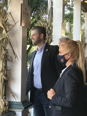 Eric Trump stands on the porch of the Dimmick Inn with police  in Milford, Pa.
