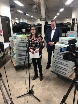Dorothy Kennedy, elections administrator, stands with county judge Curtis Parrish during a news conference on Friday. Kennedy and Parrish stood near mail ballots that were about to get mailed to voters.
