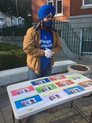 Swaranjit Singh Khalsa, member of the World Sikh Parliament and Norwich Board of Education member, displays signs in multiple languages at the City of Norwich's COVID-19 press conference Oct. 1.