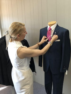 Mary Kyriakakis, also known as Mrs. K,makes sure the suit on this mannequin looks just right at Mr. and Marks K's Men's Suits and Accessories in Somerset.