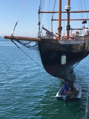 Josh Rowan and Josiah Mayo inspect the damage to the Hindu after an accident in July in Long Island Sound. For the inspection, the boat was suspended by crane at the end of MacMillan Pier in Provincetown.