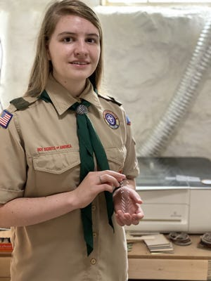 Belmont High Senior Megan Horling holds an ear saver, her Eagle Scout project inventions.