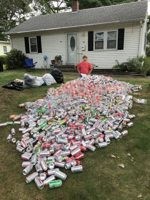 Tyler Forgeron stands with a week's worth of collected cans in his front yard. Forgeron has collected $6,300 worth of cans since the pandemic started and has donated all the proceeds to local charities.