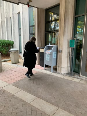 A Brookline resident drops off her mail-in ballot