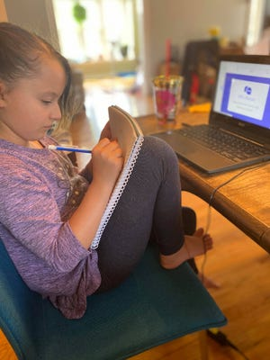 Joy Lemieux, 9 years old, takes notes during her first day of remote learning as a Hancock Elementary School student as the new school year started in Brockton on Wednesday, Sept. 16, 2020.