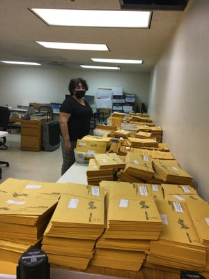 Board of Elections Chairwoman Kelly Souza-Young looks over the thousands of envelopes readied to be stuffed with ballots and sent to voters.