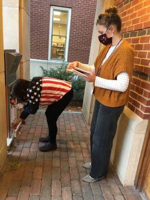 Boxford Town Clerk Robin Phelan retrieves ballots from the drop box in front of Town Hall on the afternoon of the presidential election Tuesday, Nov. 3.