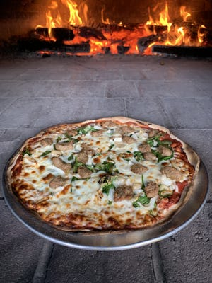 Bar 88 & Grille employee Maggie Thomas places a pizza in the wood-fired, all natural brick oven at 88 Wales St. in Taunton.