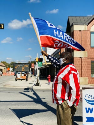 Dock Jackson, 67, clad in an American flag-print shirt, headed to Downtown Bastrop on Nov. 7, shortly after Joe Biden and Kamala Harris were projected to become the next U.S. president and vice president, and waved a flag emblazoned with their names to celebrate their historic victory.