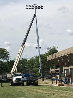Workers install one of the new light poles on the east (home) side of Memorial Stadium.