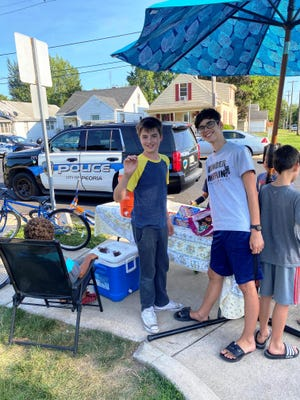 Jude Peterson, center, and his friends at their lemonade stand at California and Forrest Hill avenues in Peoria, not long after it was robbed Friday. Jude, 13, has been operaring the stand all summer, in an effort to make money and learn about business.