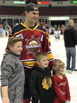 Peoria Rivermen assistant captain Ben Oskroba stops for photos with fans during a post-game skate at Carver Arena.