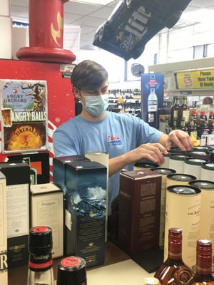Garrett Ducey stocks the shelves at the Bull River Beverage Mart. The college student is working a summer job.