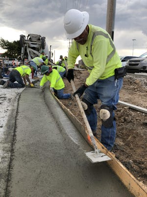 Employees of Smoky Hill Construction, Salina, lay curb and gutter on a cool, overcast Wednesday morning at the intersection of Vine and 33rd streets.