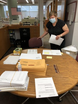 Ellis County Clerk Donna Maskus on Monday stops by a table in the county clerk's office organized with some of the individual items required for advance mail ballot envelopes.