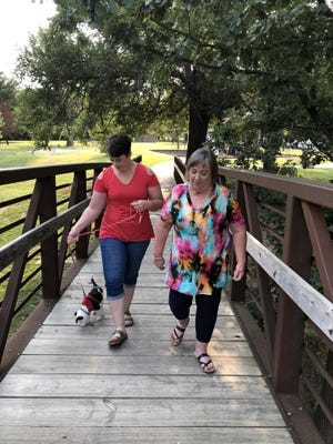 Amara Anderson, left,  and Abonne Anderson, both of Salina, walked their 10-month-old border collie puppy across the swinging bridge in Frontier Park East on Monday morning.