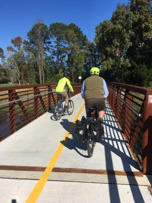 Bicyclists cross one of two bridges on the new portion of the Truman Linear Park Trail on Thursday.