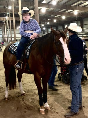 Twelve-year-old Jarrett Lippert -- a resident of Green in Clay County, who uses a wheelchair -- prepares to ride a horse in reining competition on a team sponsored by Manhattan-based Hope Ranch Therapeutic Riding Center Saturday at Stormont Vail Events Center's Domer Livestock Arena.