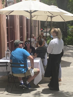 Patrons enjoy the outside seating at Savannah's Olde Pink House. The restaurant expanded its outdoor options in the wake of the coronavirus pandemic.