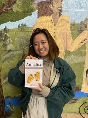 Myla Athitang holds her self-published book.