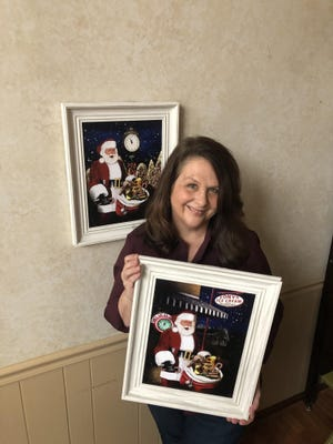 Gaston Christian School art teacher Jill Overton stands with two of her prints, which feature Gastonia's Storybook Santa and clocks from throughout the area.