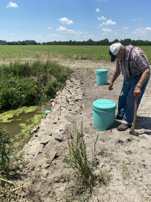 Robert Vajcner, 83, checks the two head stands near the Pin Oak Drain to determine what water levels are in the underground structures in his fields.