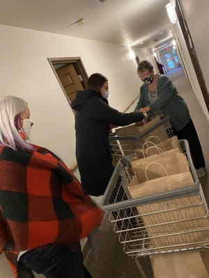 Rhayelyn Loveland, left, Rachele Bauer and Alaina Ellison, not pictured, deliver the meals door to door Christmas Eve at Wexford Manor in Onsted with the help of resident Sharon Hill.