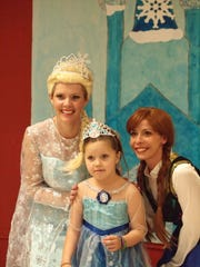 Elsa (Beth Gobbell) poses with Miriam Booker and Anna (Emily Arnold) at the Aldersgate United Methodist Church's 'Frozen Winter Carnival' Wednesday night.